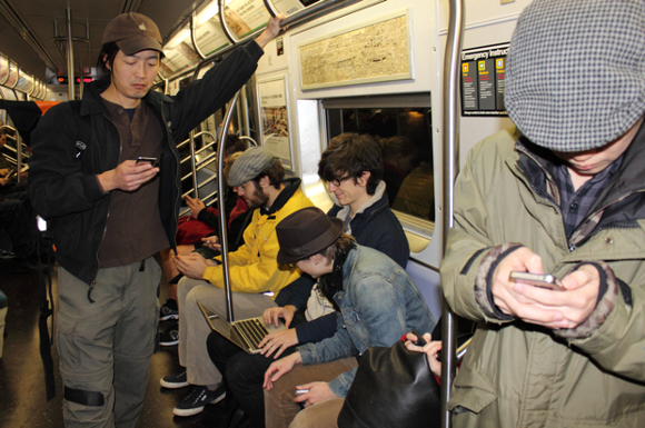 Commuters Using Phone On Subway